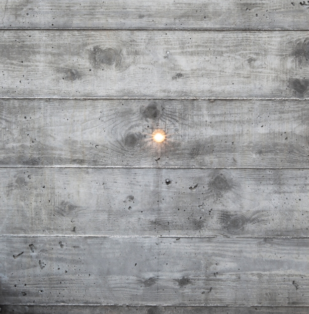 Detail of one of the many retaining walls and planters created using board formed, cast in place concrete. Light source is a tiny bronze fixture inset into the concrete and containing a small LED bulb.