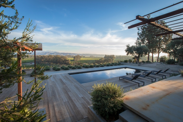Black bottom pool overlooking agricultural fields. Reclaimed wood and acid etched concrete deck. Reclaimed steel open work trellises.