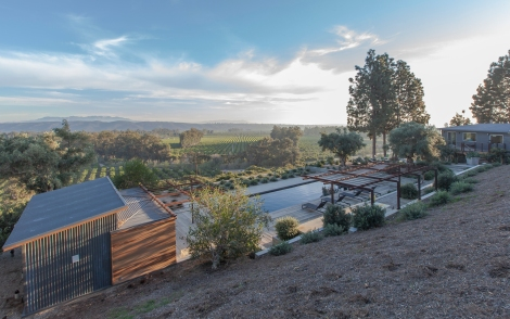 Black bottom pool overlooking agricultural fields. Reclaimed wood planks and acid etched concrete deck surround. Steel open work trellises, once planted, will provide shade for seating areas. Pool side cabana bar features a mix of corrugated steel and high fire rated cedar wood siding