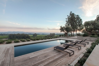 Black bottom pool overlooking agricultural fields. Reclaimed wood decking echoes the row of surrounding plantings. Board formed cast-in-place concrete retaining walls and planters contain dwarf olives and other drought tolerants varieties