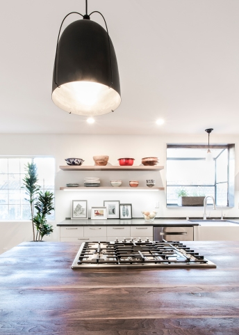Oversized pendants match the scale of the kitchen island and provide both warmth and task lighting.