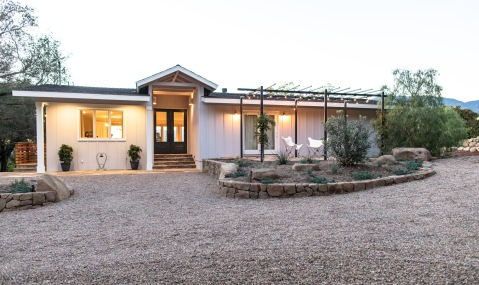 Front entrance is accessed by a gravel drive; at right, a flagstone patio off the master bedroom provides sunrise views