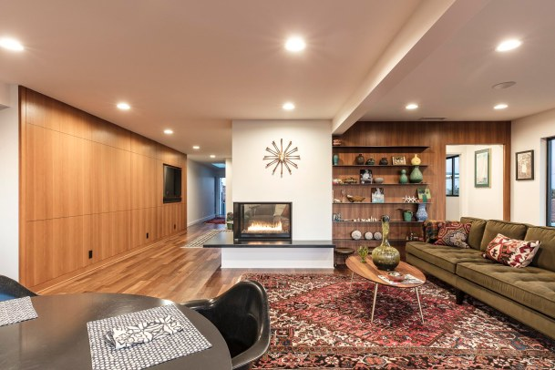 The fireplace creates separation between the main living/dining area and a small den.