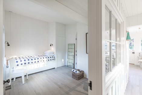 Bedroom with bleached bleached oak flooring that runs throughout the house; a limited materials palette adds size to the small-ish space