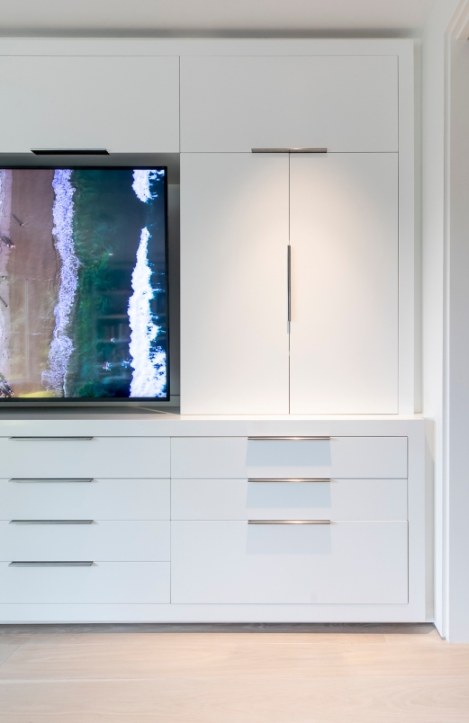 Detail of custom white-laquer entertainment center with edge-pull hardware